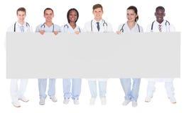 Überzeugte Doktoren, die leere Anschlagtafel halten Stockbild