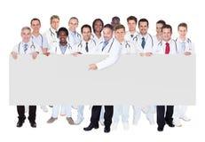 Überzeugte Doktoren gegen weißen Hintergrund Stockfotografie