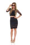 Überzeugte elegante Frau im schwarzen Kleid und in der Sonnenbrille Stockfotografie