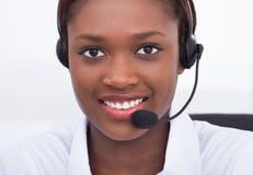 Überzeugte Empfangsdame, die Kopfhörer im Krankenhaus verwendet Stockfotos