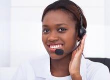 Überzeugte Empfangsdame, die Kopfhörer im Krankenhaus verwendet lizenzfreie stockfotografie
