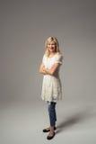 Überzeugte erwachsene Dame im weißen Kleid und in den Jeans Lizenzfreies Stockbild
