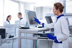 Überzeugte fokussierte Frau ist im Labor beschäftigt Stockfoto