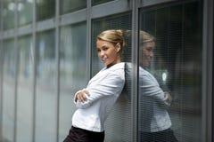 Überzeugte Frau, die auf Bürohausfenster sich lehnt Lizenzfreie Stockbilder