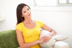 Überzeugte Frau, die auf der Couch sitzt stockfotografie