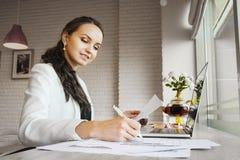 Überzeugte Frau, die bei Tisch sitzt und Kenntnisse auf Papier nimmt Lizenzfreie Stockbilder