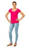 Überzeugte Frau, die mit den Händen auf Hüften steht Stockfoto