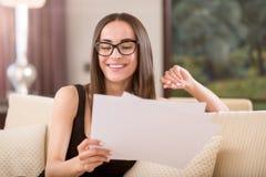 Überzeugte Frau, die Papiere betrachtet Lizenzfreie Stockfotografie