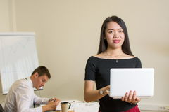 Überzeugte Frau mit einem Laptop im Büro Stockbilder