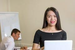 Überzeugte Frau mit einem Laptop im Büro Lizenzfreie Stockfotografie
