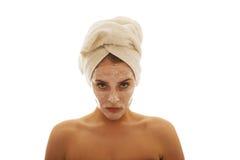 Überzeugte Frau mit Gesichtscreme Lizenzfreie Stockfotos