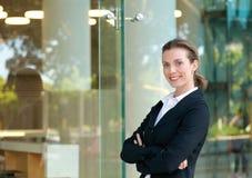 Überzeugte Geschäftsfrau, die durch Glasfenster lächelt Stockbild