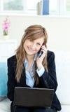 Überzeugte Geschäftsfrau, die einen Handy verwendet Stockbild