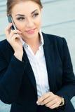 Überzeugte Geschäftsfrau, die am Geschäftstelefon spricht lizenzfreies stockbild