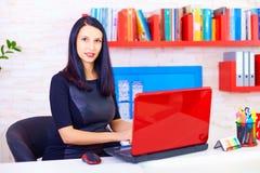 Überzeugte Geschäftsfrau, die im Büro arbeitet Stockbild