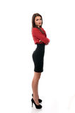 Überzeugte Geschäftsfrau, die mit ihren Armen gefaltet aufwirft Stockbild