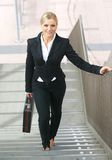 Überzeugte Geschäftsfrau, die oben mit Tasche geht Lizenzfreies Stockbild