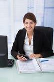Überzeugte Geschäftsfrau, die Taschenrechner am Schreibtisch verwendet Stockbild