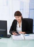 Überzeugte Geschäftsfrau, die Taschenrechner am Schreibtisch verwendet Stockfotografie