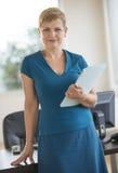 Überzeugte Geschäftsfrau With File Standing am Schreibtisch Stockfotos