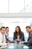Überzeugte Geschäftsfrau mit ihrem Team an einem Tisch Lizenzfreie Stockfotos