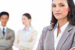 Überzeugte Geschäftsfrau mit Kollegen hinter ihr Stockbilder