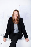 Überzeugte Geschäftsfrau Sitting On Counter im Büro Stockfotografie