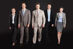 Überzeugte Geschäftsleute, die gegen schwarzen Hintergrund gehen Stockfoto