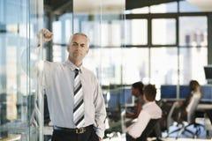 Überzeugte Geschäftsmann-Leaning On Glass-Tür stockbilder