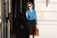 Überzeugte hübsche Frau in der Sonnenbrille unter Verwendung des Handys lizenzfreie stockbilder