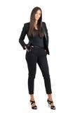 Überzeugte herrische Geschäftsfrau im schwarzen Anzug mit den Händen in den Taschen, die Kamera betrachten Stockbilder