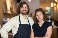Überzeugte Inhaber, die zusammen im Café stehen Lizenzfreie Stockbilder