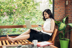 Überzeugte junge asiatische Frau in der intelligenten Freizeitkleidung unter Verwendung des Laptops Stockfotografie