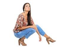 Überzeugte Junge bräunten Brunette, den das Mode-Modell, das in den Jeans mit aufwirft, zurück vorangehen Stockfotos