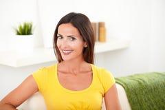 Überzeugte junge Frau, die auf der Couch sitzt lizenzfreie stockfotos