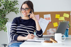 Überzeugte junge Frau, die in ihrem Büro mit Handy arbeitet Lizenzfreie Stockfotos