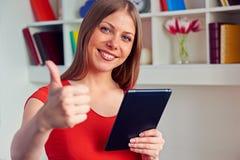 Frau, die Tablette-PC hält und sich Daumen zeigt Stockbild