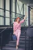 Überzeugte junge Frau hagelt ein Taxi stockbilder
