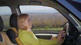 Überzeugte junge Frau trinkt Kaffee am Steuer eines Autos Langsame Bewegung stock video