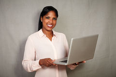 Überzeugte junge Geschäftsfrau, die einen Laptop hält Lizenzfreies Stockfoto