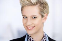 Überzeugte junge Geschäftsfrau Smiling In Office Stockbilder