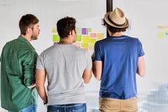 Überzeugte junge Männer, die Informationen über kleine Papiere besprechen lizenzfreie stockbilder