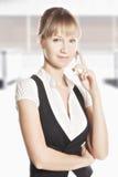 Überzeugte kaukasische Frau am Telefon im Büro Lizenzfreies Stockfoto