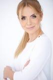 Überzeugte lächelnde blonde Frau im weißen Hemd Stockfoto
