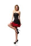 Überzeugte lächelnde elegante Frau im Kleid, das in voller Länge steht stockfoto
