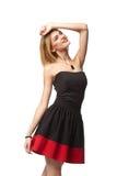 Überzeugte lächelnde elegante Frau im Kleid, das in voller Länge steht stockfotos