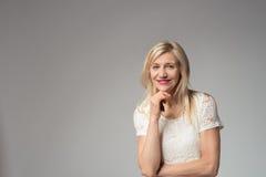 Überzeugte lächelnde Frau auf Grau mit Kopien-Raum Stockbilder