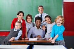 Überzeugte Lehrer mit Schulkindern zusammen an Stockfoto