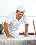 Überzeugte männliche Bäcker-Cleaning Flour From-Tabelle Stockfotos