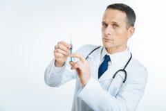 Überzeugte medizinische Arbeitskraft mit der Spritze, die Kamera untersucht Stockfotos